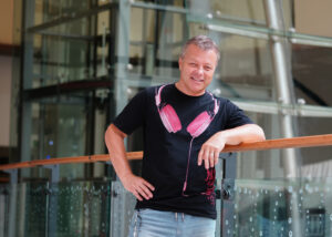 DJ Milan Šifta v tričku s růžovými sluchátky
